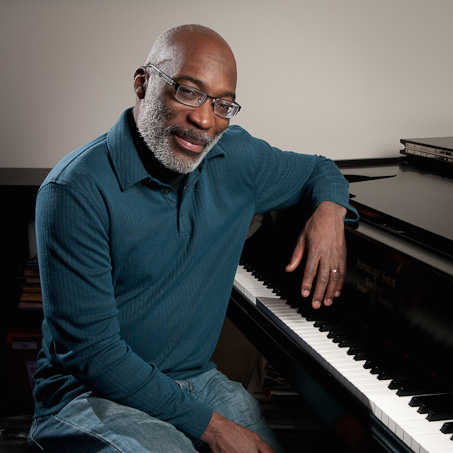Portland jazz pianist Darrell Grant poses at the piano in his office at Portland State University Dec. 5, 2011. (Photo by Matthew Ginn for NW Boomer & Senior News)
